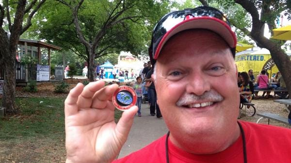 Jeff Mullin shows his east-side pride coin on East Side Night at the Iowa State Fair on Friday.