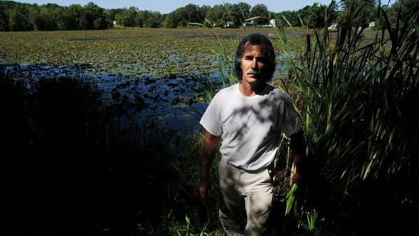 Robert Grasso of the Hillside Lake community stands on the edge of Hillside Lake where drainage from the road enters the lake in the Town of East Fiskill.
