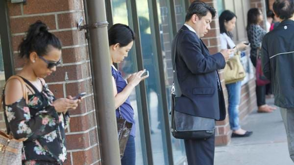 Larry Delacruz of White Plains uses his mobile device while waiting for the train at the White Plains Metro-North Station on June 4, 2014.