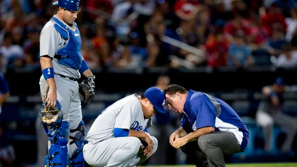 A member of the Los Angeles Dodgers training staff talks to injured starting pitcher Hyun-Jin Ryu (99) as catcher A.J. Ellis looks on at left, in the sixth inning of a baseball game against the Atlanta Braves Wednesday, Aug. 13, 2014, in Atlanta. Ryu left the game under his own power.