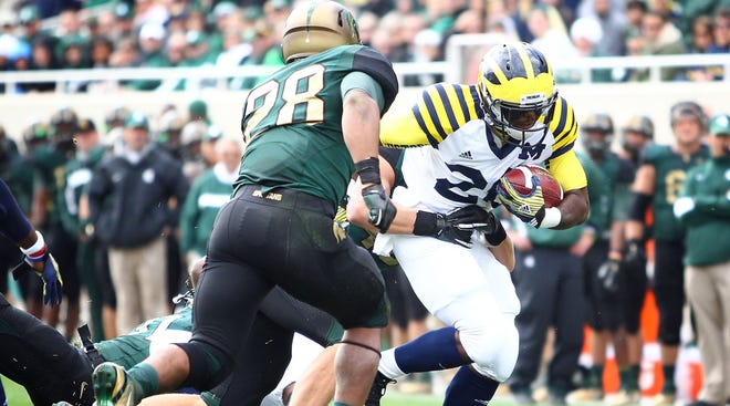 Ex-Michigan Wolverines wide receiver Darryl Stonum (22) is stopped short of goal line in first quarter of the game against the Michigan State Spartans at Spartan Stadium. Stonum, 24, was convicted on Wednesday of two misdemeanor counts of domestic violence and one count of felonious assault.