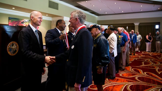 Gov. Rick Scott shakes hands with local veterans while presenting them with the Governor's Veterans Service Award at the Bonita Bay Club on Monday, April 10, 2017.