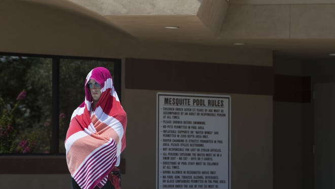 Lifeguard Chris McCow covers himself from the sun at the Mesquite Aquatic Center on July 7, 2017, in Gilbert.