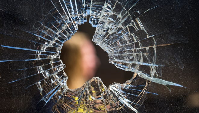 A north-central Phoenix resident is seen through a bullet hole from a bedroom of her home. The home has been targeted on four different occasions. Several nearby houses have also been shot with the same .44 magnum gun, with one neighbor being hit in the arm. Police are stumped, and the homeowners are nervous.