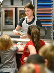 Grace Gilmore, 12, serves about 370 turkey wraps Thursday, Feb. 11, 2016, to students at Clearview Elementary School. A group of students created a volunteer program to help the kitchen staff.