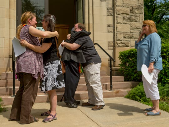 From left, Senior Pastor Kirianne Riehl, Rabbi Suzanne Brody, Rabbi Scott Glass, Associate Pastor John McDonald and Kate Hubbs take turns hugging Wednesday afternoon after reading the names of the 49 victims of the Pulse nightclub shooting from the front steps of the First Presbyterian Church  in Ithaca.