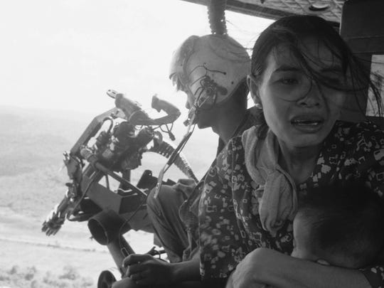 A refugee clutches her baby as a government helicopter gunship carries them away near Tuy Hoa, 235 miles northeast of Saigon in March 1975. They are among thousands fleeing from recent Communist advances.