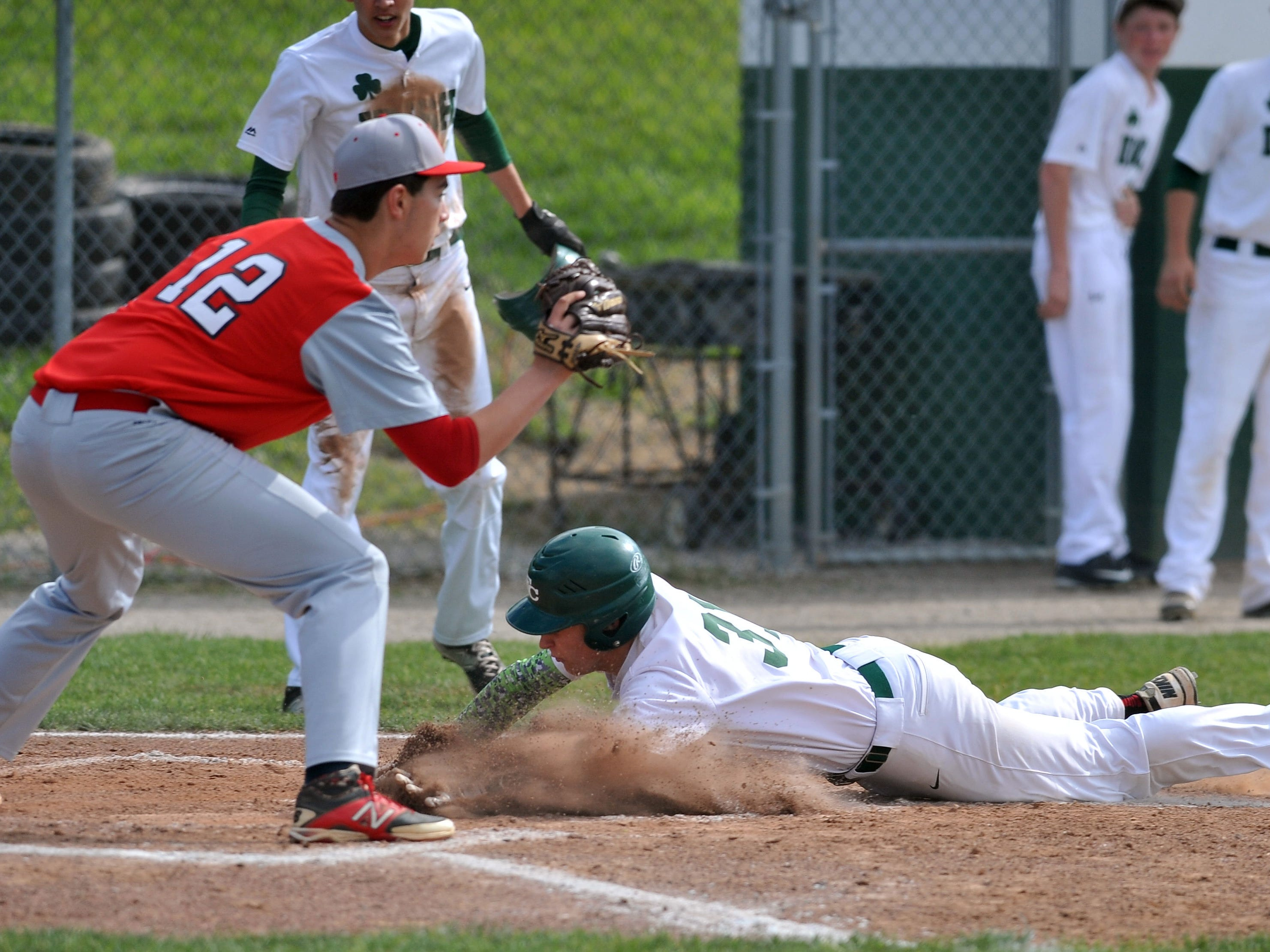 Fisher Catholic's Blake Saffell slides safely into home Wednesday night in Lancaster. The Irish defeated Fairbanks 5-2.