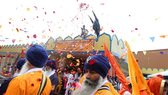 Colorful rose petals are tossed from the roof of the Gurdwara as part of the 10th annual Dasmesh Darbar Sikh Temple Parade on Saturday, June 18, 2016, in South Salem. The celebration commemorates Sri Guru Arjan Dev Ji Sahib's Martyrdom Day.