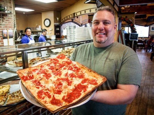 Jerry LoPresti (above) holds his signature Brooklyn Sicilian pizza. He and his father Nino are owners of LaPiazza.