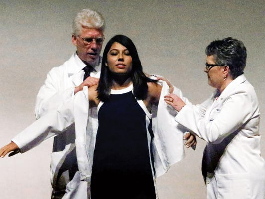 Desiree Carmen of El Paso is cloaked in a physician's coat during a white coat ceremony for students of the Class of 2019 entering the Paul. L. Foster School of Medicine Saturday at the Plaza Theatre. Helping her is Richard Lange, M.D., left, founding president of Texas Tech University Health Science Center at El Paso and Dean of the Paul L. Foster School of Medicine; and Kathryn V. Horn, M.D., assistant vice president for Student Services and Associate Dean for Student Affairs at Texas Tech HSC El Paso.