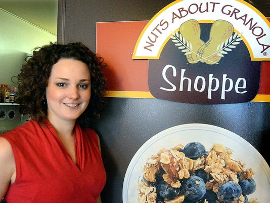 Sarah Lanphier poses in her Nuts About Granola Shoppe. Below is the storefront on West Philadelphia Street.