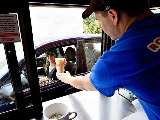 Shift lead Chris Simms, right, serves Jaycie Hoke of New Salem at the Dunkin' Donuts drive-thru Friday on Loucks Road. Customers at that location regularly pay it forward to fellow customers.