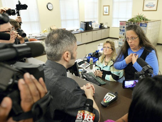 Rowan County Clerk Kim Davis, right, talks with David Moore following her office's refusal to issue marriage licenses at the Rowan County Courthouse in Morehead, Ky., Tuesday, Sep. 1, 2015. Although her appeal to the U.S. Supreme Court was denied, Davis still refuses to issue marriage licenses. (AP Photo/Timothy D. Easley)