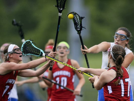 FILE — GAMETIMEPA.COM Kennard-Dale's Madeline Day shoots through the defense of Susquehannock's Gena Speights, left, and Michella Salvitti during a District 3 girls' lacrosse game in May at Lower Dauphin Middle School. The PIAA is considering expanding lacrosse from one to two classifications.