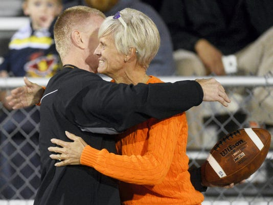Kate Penn — GameTimePA.com York Suburban athletic director Chris Adams gives the game ball to superintendent Shelly Merkle, mother of York Suburban's Thomas Merkle, after he broke the school's all-time passing record.