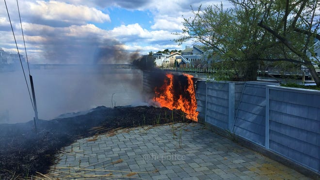 A brush fire that spread to a fence in Harvey Cedars on Tuesday.