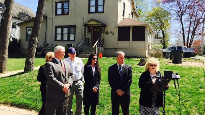Rockland Health Commissioner Patricia Ruppert discusses plans for a crackdown on illegal and substandard housing as Rockland County Executive Ed Day and program leader Catherine Johnson and other officials stand to her right. Behind them is a house at 76 Fairview Ave. in Spring Valley with 19 sanitary code violations.