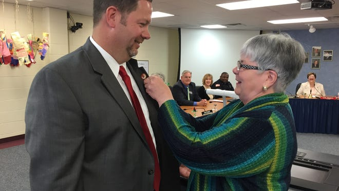 School board member Dixie Robinson pins a Richmond Community Schools badge to the lapel of new superintendent Todd Terrill during a special meeting to approve his contract Tuesday.