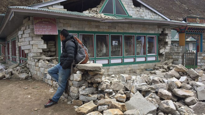 Mingmar Sherpa, one of the men guiding the group of trekkers led by David Carter, stands in front of a damaged lodge in Pheriche on April 26.