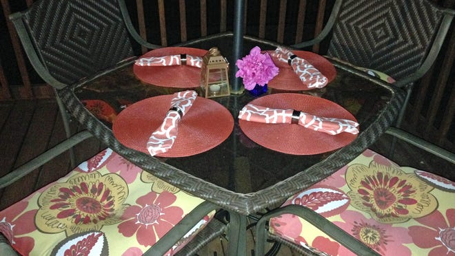 Accessorize outdoors with colorful placemats, cloth napkins and seat cushions. You can find deals by shopping at yard sales and on local buy-sell-trade websites.