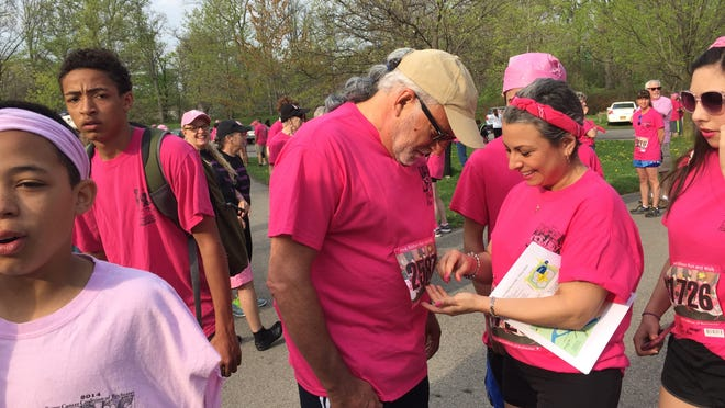 Michele Levy of Pittsford pins a number onto the shirt of brother-in-law David Levy as the family gets ready for the Breast Cancer Coalition of Rochester Pink Ribbon Run & Family Fitness Walk Sunday, May 10, 2015, at Genesee Valley Park.