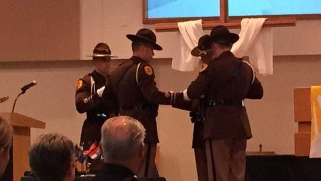 Members of the Iowa State Patrol Honor Guard fold the American flag during the Peace Officers Memorial Service on Tuesday at Aldersgate United Methodist Church in Urbandale .