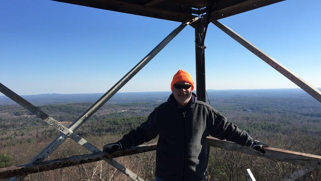 John Kravic, Jr. poses at the top of a small mountain in New Hampshire, hiking with his son John Kravic III.