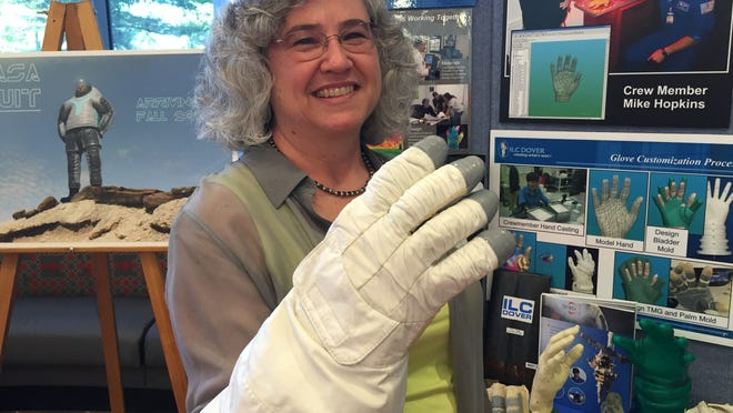 Jinny Ferl, a design engineering manager for ILC Dover in Frederica, shows off the glove from one of the Apollo spacesuits during the inaugural Top Tech Trends event in Wilmington on Wednesday.