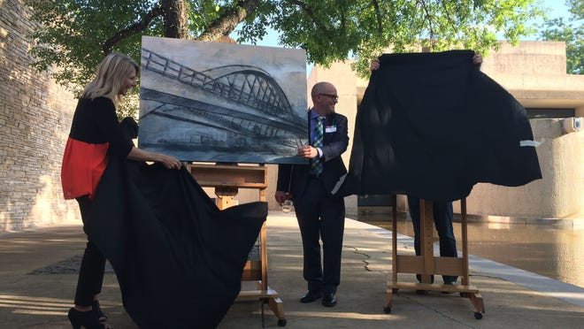 Des Moines Arts Festival board chair Natalie Tomaras and Des Moines Register publisher David Chivers unveil the original multimedia work for this year's festival during a ceremony Thursday in the Des Moines Art Center courtyard. The artist, Benjamin Frey, unveiled the poster on the right.