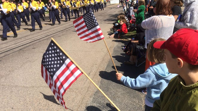 Calder Rakowski, 9, and Hazel Rakowski, 6, both of Vergennes, wave flags Saturday during the Essex parade.