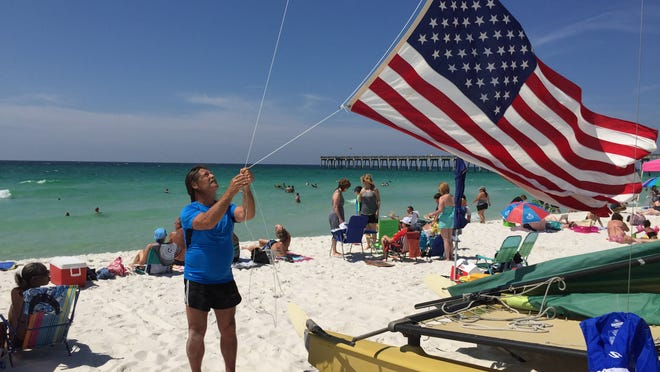 George McIntosh, 64, of Leslie, Ark., hoists the flag that draped the casket of his late father, Joe Daniel McIntosh, on his Hobie Cat catamaran in Pensacola Beach Saturday. Flying the flag from the catamaran is his way of paying tribute to members of the armed forces who sacrificed their lives for the country.