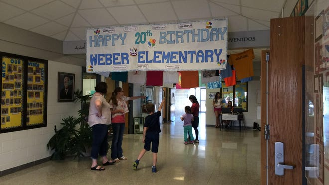 Past and present students and employees gather Sunday, May 31 for the 20th anniversary celebration of Weber Elementary School which included ice cream, a steel drum band and a display of artifacts from a time capsule buried at the school in 1995.