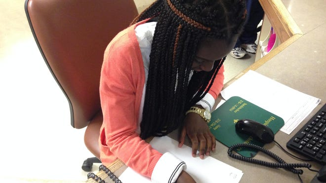 Raymonde Armoo writes down a message from a patient while volunteering at Christus St. Frances Cabrini Hospital.