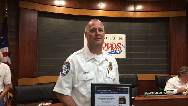 Wisconsin Rapids Deputy Fire Chief Scott Young shows the 2015 Mission Lifeline Award Tuesday night at the Wisconsin Rapids City Council meeting. The American Heart Association presented the award to the department for its care of heart attack victims.