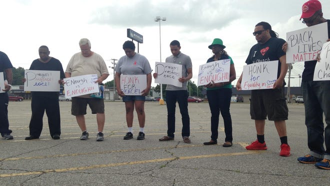 In this file photo, marchers pray in the parking lot of the old K-Mart building on Old Hickory Boulevard before marching down the U.S. 45 Bypass.