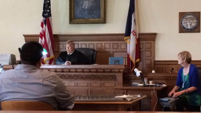 Jorge Perez, 23, of Iowa City, left, listens to Judge Mitchell Turner, center, during a plea hearing at the Johnson County Courthouse Wednesday afternoon.