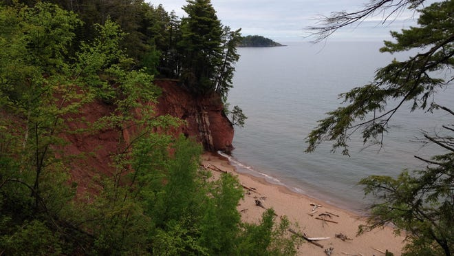 Sandstone cliffs and a hidden beach along the shoreline of Lake Superior on the North Country Trail near Marquette, Michigan.