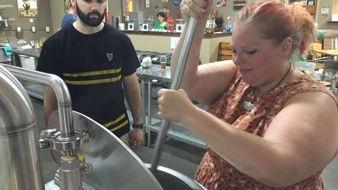 Brewmaster Lou Luzzo instructs APP designer Jen Meyer as she stirs the Sweet Caroline IPA brewing in the kettle.