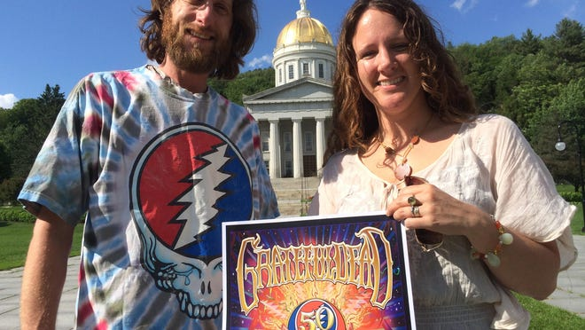 Mitch Pauley, wearing a Grateful Dead T-shirt, and Rachel Carter, holding a Grateful Dead 50th anniversary poster, stand in front of the Vermont Statehouse in Montpelier. The Plainfield couple will head to Chicago for the Dead's final concerts July 3-5.