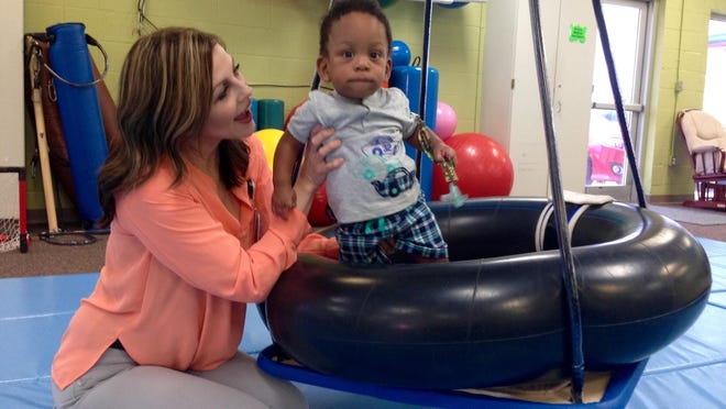 Speech language pathologist Melissa McTire helps Kingston Cooper, 1, balance on a moving tire swing Friday at the Pediatric Therapy Center of Christus St. Frances Cabrini Hospital. Kingston is learning to crawl and take steps with a prosthetic leg.