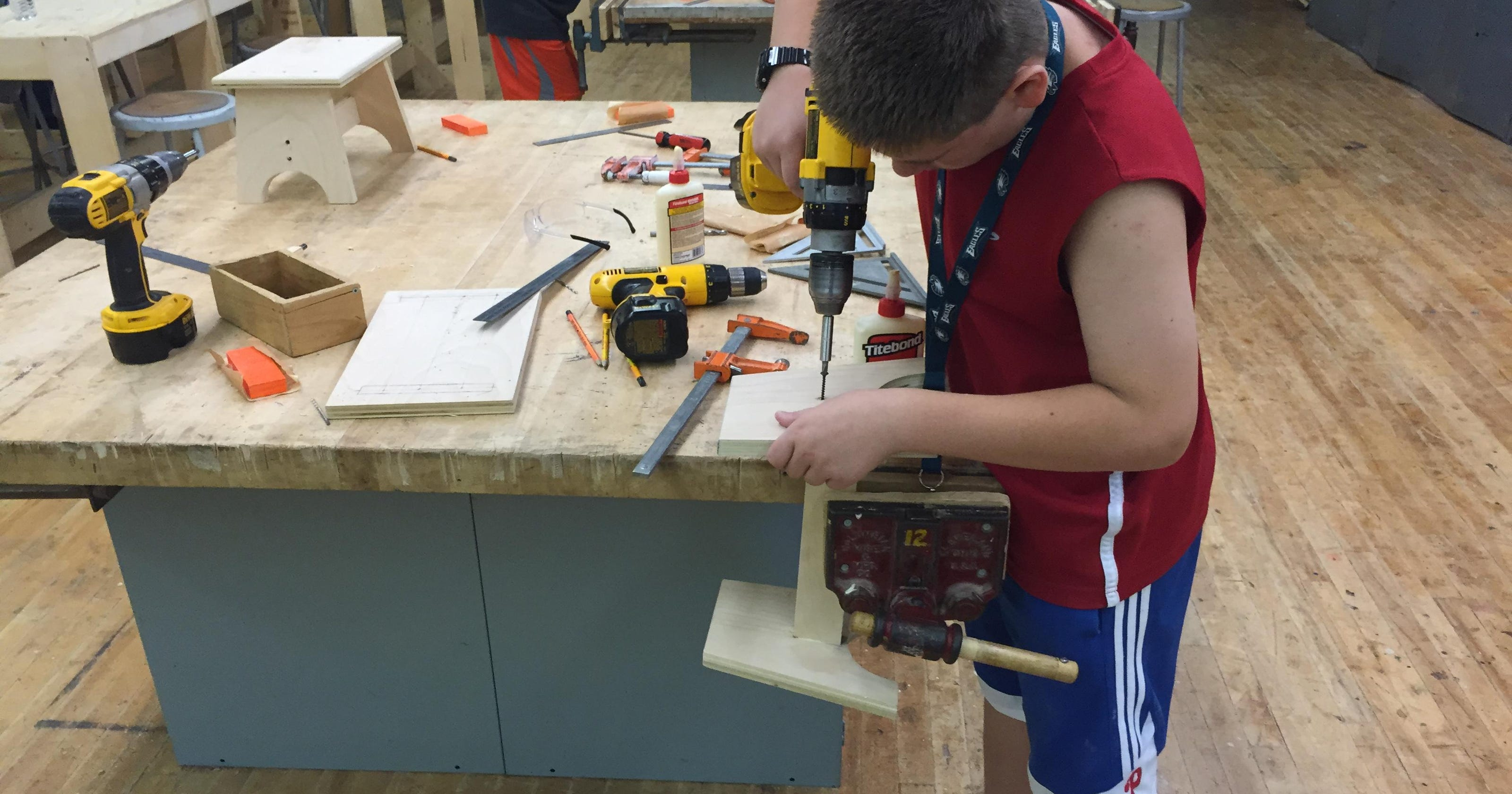 Kids weld, saw and hammer in construction camp