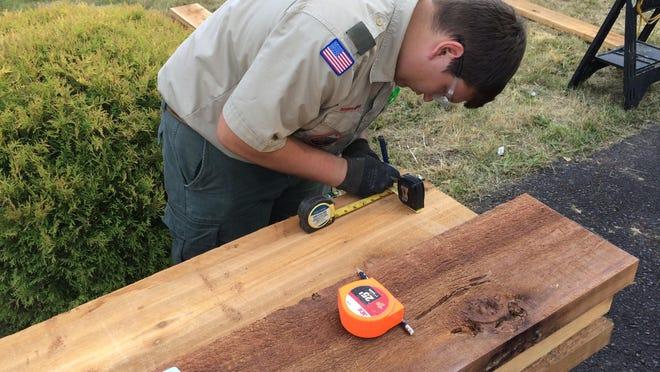 Teegan LaRochelle, 17, measures wood for a raised garden bed.