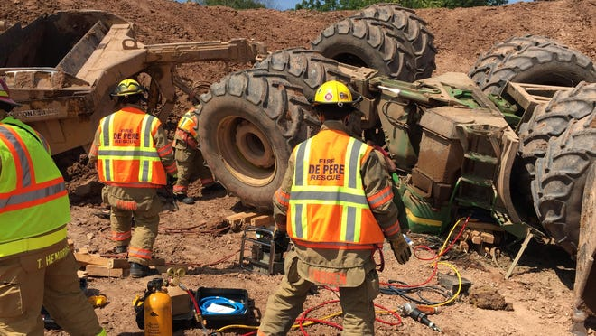 Firefighters work on an overturned tractor at a Ledgeview dairy farm on July 8, 2015. The tractor was pulling a trailer when it overturned, trapping the operator for 90 minutes.