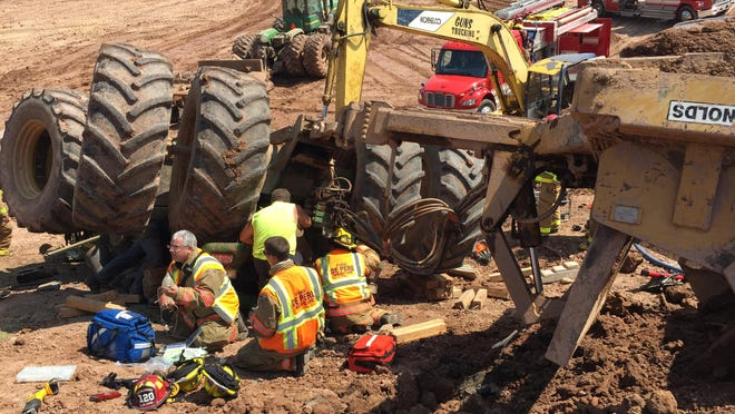 Firefighters work at the scene of an overturned tractor at a Ledgeview dairy farm on Wednesday. The tractor was pulling a trailer when it overturned, trapping the operator, Jason Pansier, for 90 minutes inside the vehicle's crushed cab.
