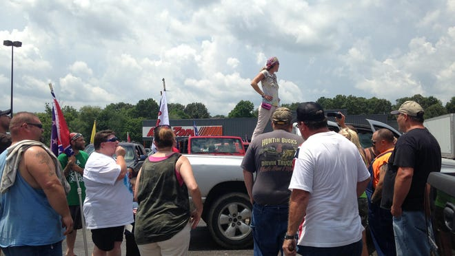Protesters gather in the AutoZone parking lot in Camden to hear final instructions and pray before beginning a rally on Sunday. The group were part of a protest organized by Confederate Warriors, who are opposed to renaming Nathan Bedford Forrest State Park.