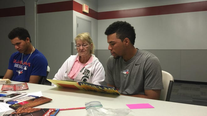 Lansing Lugnuts pitcher Jose Fernandez, left, and Carol Walker listen as catcher Michael De La Cruz reads during an English class Tuesday. International players on the Lansing roster get English instruction on days of home night games.