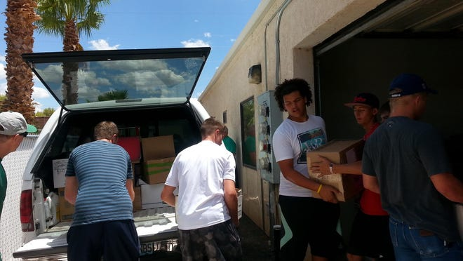 Football team members form an assembly line to load books into a truck bed.