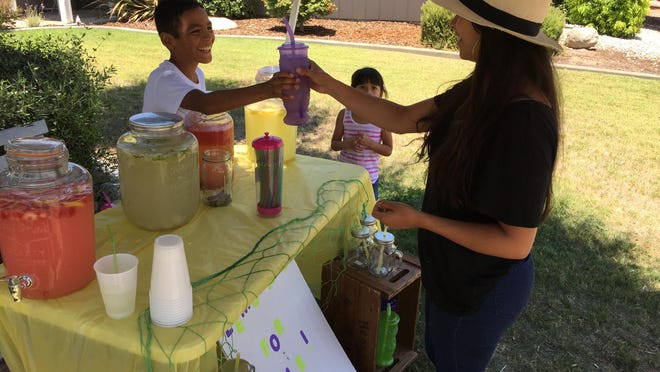 Cisco Cabrera, 11, hands cup of lemonade to Jessica Bermudes at his stand on County Center and Evergreen in Visalia to help get him to Michigan for a wrestling tournament.