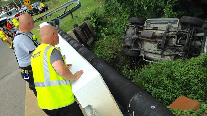 Emergency personnel look down on a vehicle that left the road, crashed through a guardrail and overturned Sunday afternoon. One person was medevaced from the scene to Jersey Shore University Medical Center in Neptune.